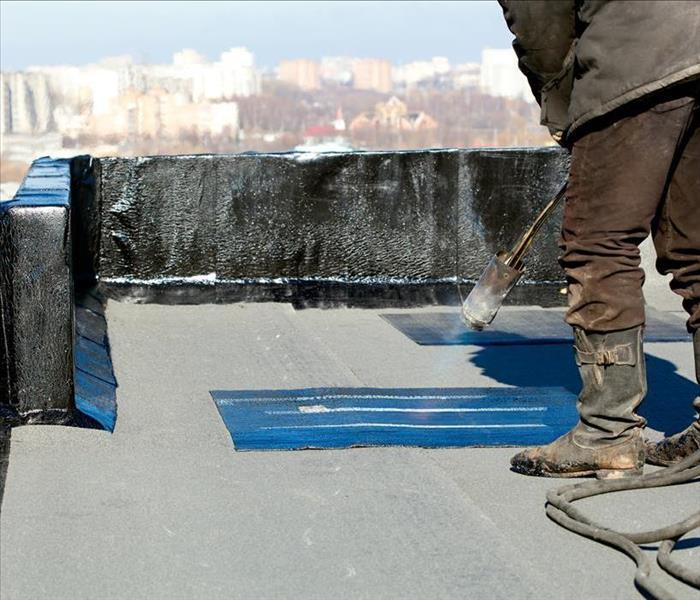 Image of a person performing maintenance on roof of a property